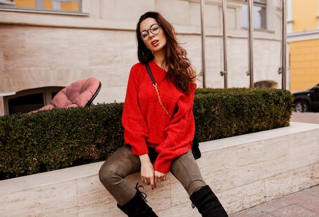 Великолепная успешная брюнетка женщина позирует на открытом воздухе в модном весеннем наряде. модные сапоги, красный стильный свитер. старый европейский город.