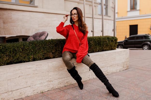 ゴージャスな成功したブルネットの女性がトレンディな春の服装で屋外でポーズします。おしゃれなブーツ、赤いスタイリッシュなセーター。古いヨーロッパの都市。