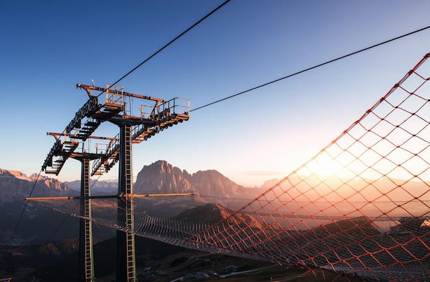 Gorgeous sunset. cableway standing on the hills in seceda dolomites.