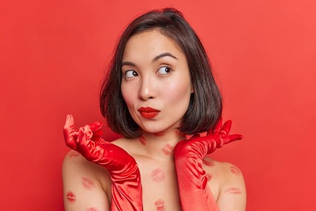 La splendida donna asiatica premurosa con i capelli scuri sembra pensierosa, indossa eleganti guanti lunghi, ha labbra dipinte di rosso, tracce di baci sul corpo posa abiti al coperto per un appuntamento romantico