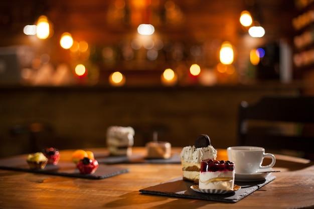コーヒーショップの木の板の上にさまざまな味のさまざまなケーキのゴージャスな景色。コーヒーショップで美味しいケーキのバラエティ。おいしい一杯のコーヒー。