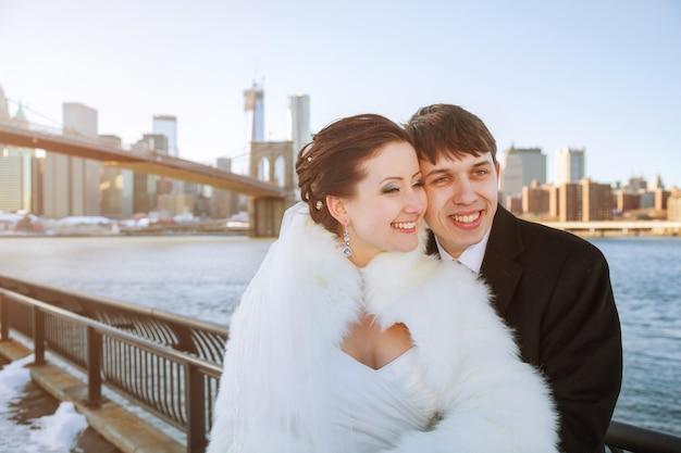 クラクフの橋でポーズをとってゴージャスな結婚式のカップル、新郎新婦