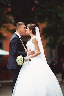 豪華な結婚式のカップルは建築のある旧市街で晴れた日を楽しんでいます