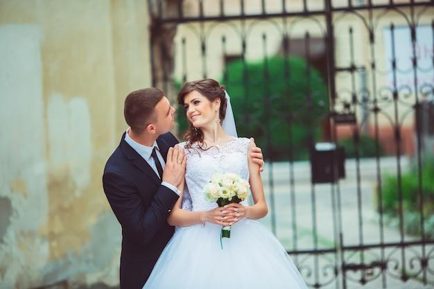 豪華な結婚式のカップルは、建築のある旧市街で晴れた日を楽しんでいます