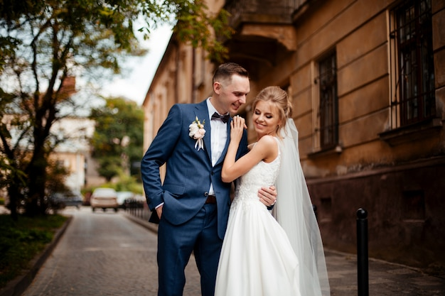 街を歩いて豪華な結婚式のカップル。スタイリッシュなスーツの新郎と美しい白いドレスの花嫁