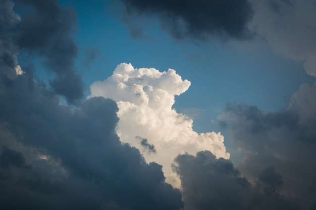 Gorgeous white cloud comes through many other dark blue clouds in the sky after the rain