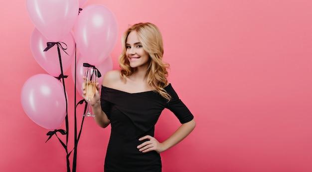 분홍색 벽에 샴페인 잔을 들고 화려한 백인 여자. 파티 풍선과 함께 포즈를 취하는 동안 와인을 즐기는 물결 모양의 헤어 스타일을 가진 아름 다운 아가씨.