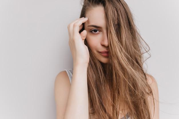 落ち着いた表情でポーズをとるゴージャスな白人少女。孤立した長い髪の素晴らしい女性モデルの屋内の肖像画。