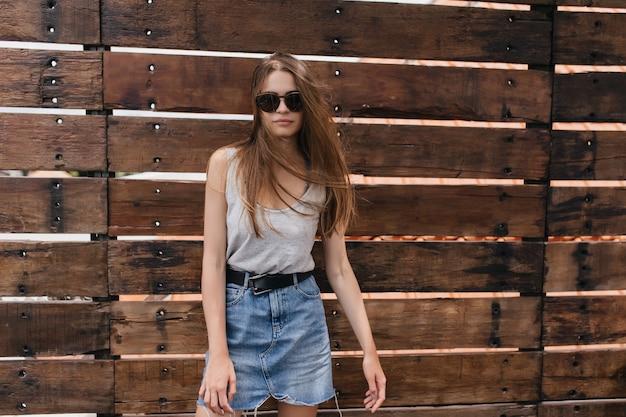 Splendida ragazza bianca in gonna di jeans vintage in posa sulla parete di legno. colpo esterno di grave giovane donna dai capelli lunghi.