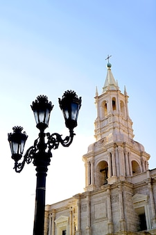 Gorgeous  white volcanic stone bell tower of basilica cathedral of arequipa with vintage black iron lamppost, arequipa, peru