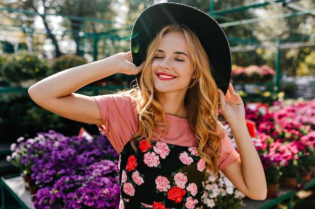 オレンジリーに笑みを浮かべて帽子をかぶったゴージャスな白人女性。ガーデニングを楽しんでいる陽気な女性の肖像画。