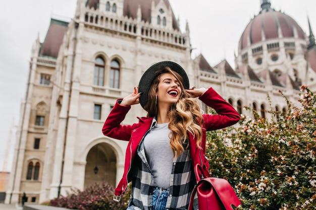 Splendida donna bianca che tocca il suo cappello mentre posa vicino al vecchio luogo storico