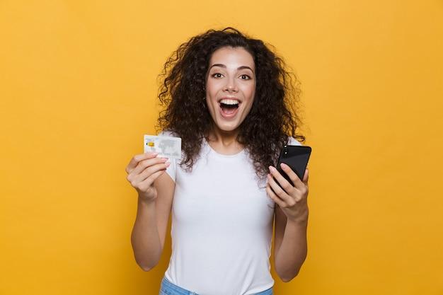 Великолепная женщина 20 лет в повседневной одежде держит мобильный телефон и кредитную карту, изолированную на желтом