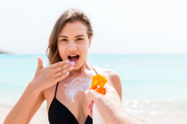 해변에서 자외선 차단제를 적용하는 화려한 여자