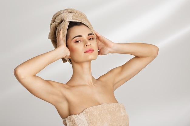화려한 여자는 수건으로 덮여 있습니다. 스파 절차 후 이마에 손으로 서