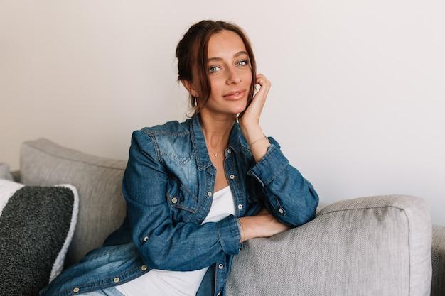 Splendida donna in camicia di jeans in posa su sfondo bianco a casa