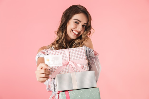 Gorgeous woman in dress holding credit card and boxes with purchase, isolated on pink