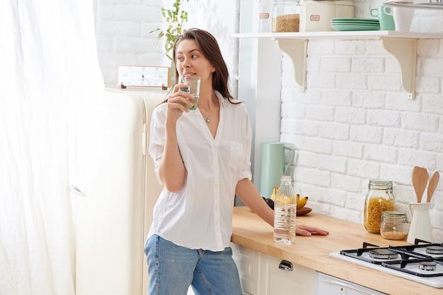 ゴージャスな女性は彼女のキッチンで水を飲む