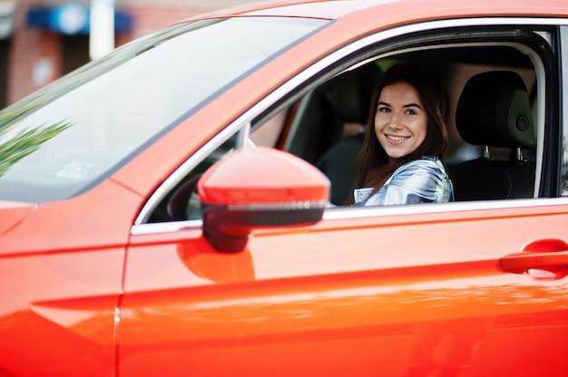 オレンジ色のsuv車を運転するゴージャスな女性
