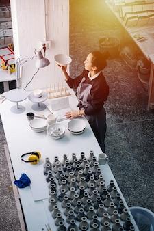 새로 생성 된 빈 식기와 꽃병이있는 테이블 뒤에 램프 아래에서 그릇을 검사하는 화려한 여자