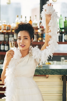 Gorgeous woman in fancy dress and boa standing with a champagne flute in the bar