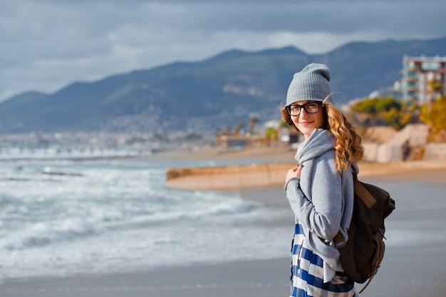 Gorgeous woman in gray hoodie and hat standing and smiling in beach during daytime with sea