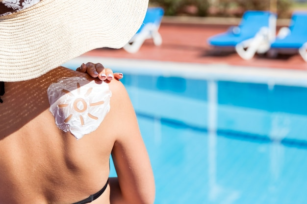 Gorgeous woman has a sun shaped sunblock on her shoulder by the pool. sun protection factor in vacation, concept.