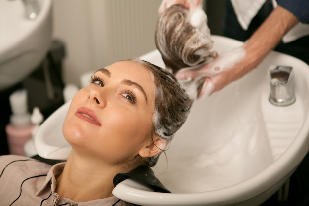 Gorgeous woman having her hair washed by hairdresser