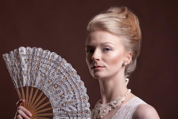 스튜디오 사진에서 갈색 배경에 동양 부채를 들고 있는 멋진 여성. 로코코 스타일. 빈티지함과 화려함