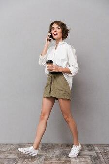 テイクアウトコーヒーを保持し、スマートフォンで話しているゴージャスな女性、灰色の壁に隔離