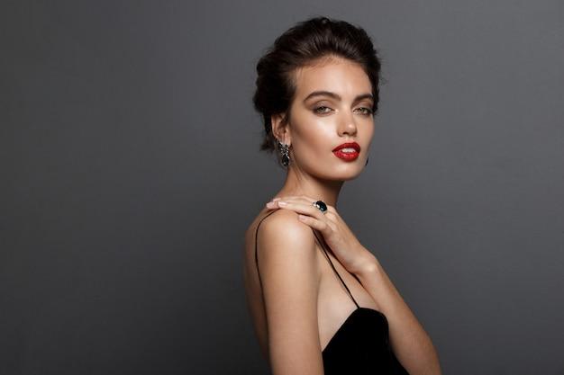Великолепная женщина в черном платье с голой спиной