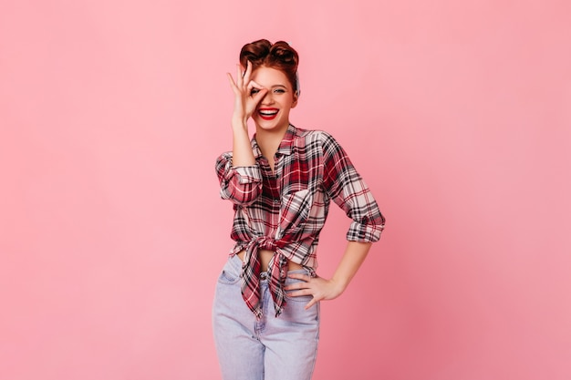 大丈夫な兆候を示すジーンズのゴージャスな女性。ピンクの空間で身振りで示すピンナップガールを笑う。