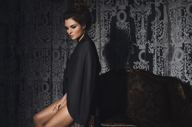 男性のジャケットを着て豪華な部屋でゴージャスな女性