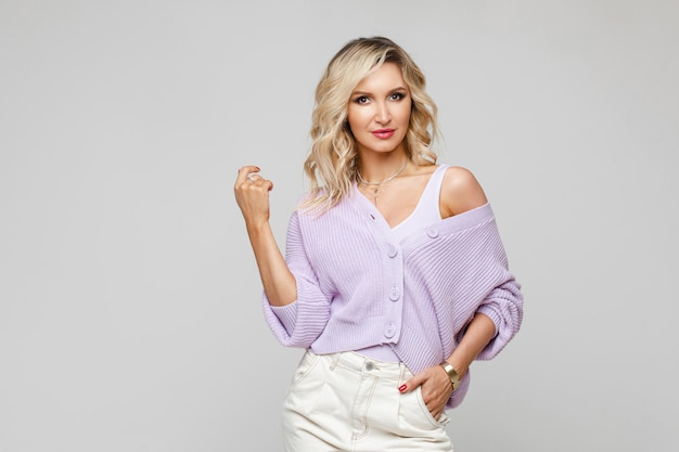 ピンクのタイトなトップのゴージャスな女性。ピンクのトップと紫の底を身に着けている金髪のウェーブのかかった髪のスタイリッシュな美しい若い女性のファッションの肖像画。