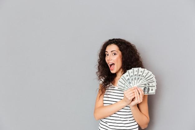 Великолепная женщина в полосатой футболке держит веер 100 долларовых банкнот в руках, улыбается на камеру, будучи счастливым и счастливым за серую стену