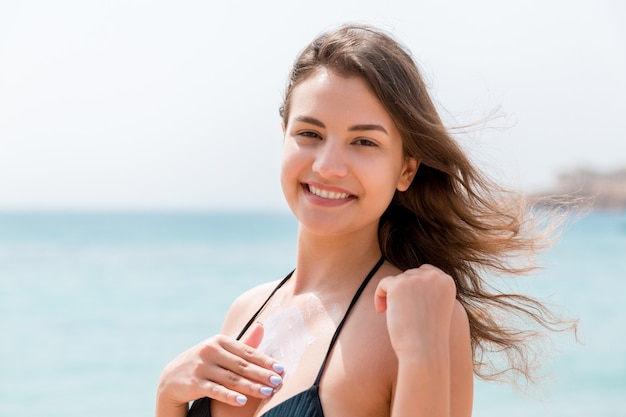 Gorgeous woman is applying sun cream on her breast with the fingers at the sea background.