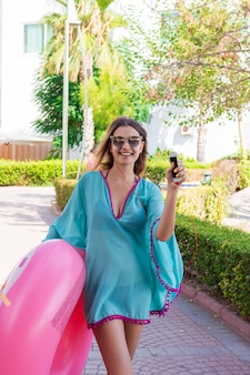 Gorgeous woman is going to the beach with an inflatable circle listening