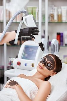 Великолепная женщина, лежащая в спа-салоне в защитных очках и угольной маске, и рука косметолога, держащая красавицу апарат возле лба