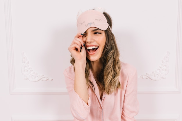 Gorgeous woman in pink pajama posing on wall