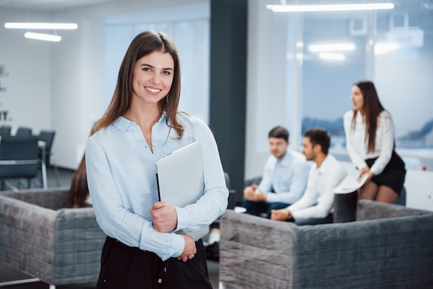 Gorgeous woman. portrait of young girl stands in the office with employees at background
