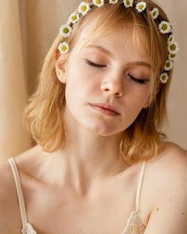 봄 꽃 왕관을 착용하는 동안 포즈를 취하는 화려한 여자