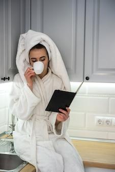 ゴージャスな女性がキッチンで朝をリラックスし、コーヒーを飲みながらリラックス。快適なホームレジャー。