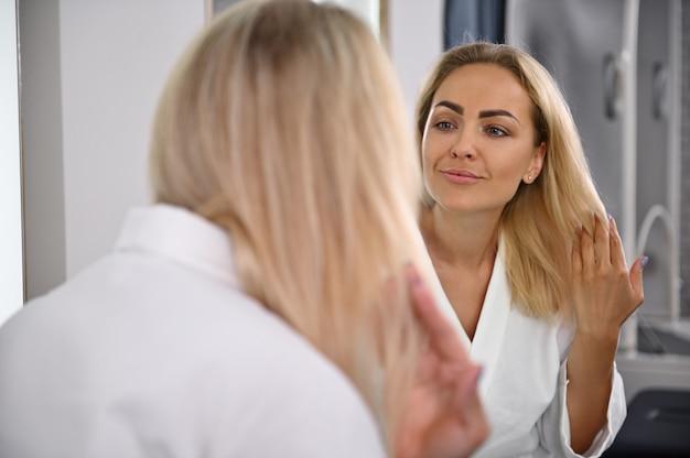 美容センターの鏡の前に立って、見た目と髪型に満足したゴージャスな女性