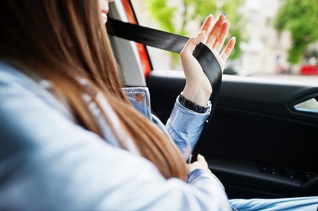 車内とネクタイベルトの中に座っているゴージャスな女性
