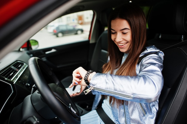 車のインテリアの中に座っているゴージャスな女性、彼女の時計を見てください