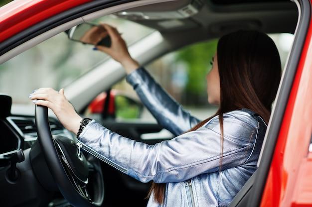 開いたドアで車の中に座って、鏡を見ているゴージャスな女性