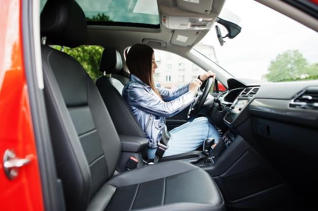 開いたドアで車の中に座っているゴージャスな女性