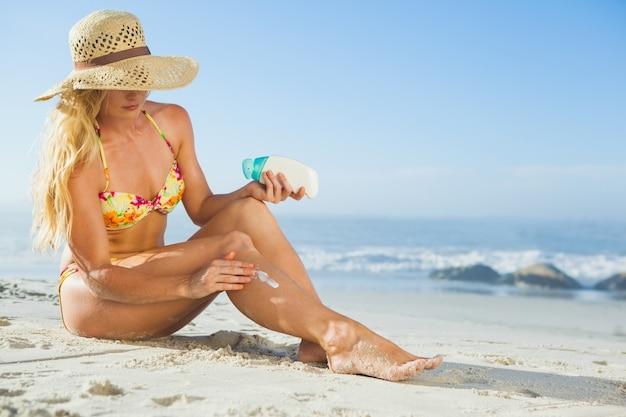 Великолепная женщина, сидя на пляже в sunhat применения suncream