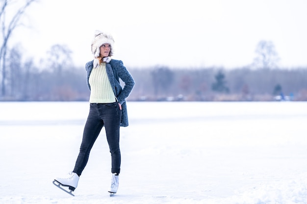 Gorgeous woman skating on frozen lake in winter