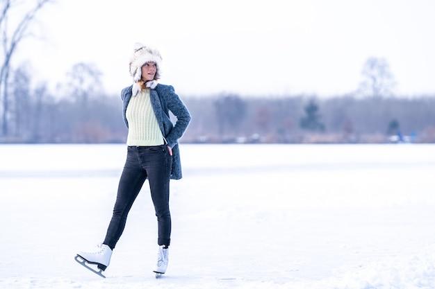 冬に凍った湖でスケートをするゴージャスな女性